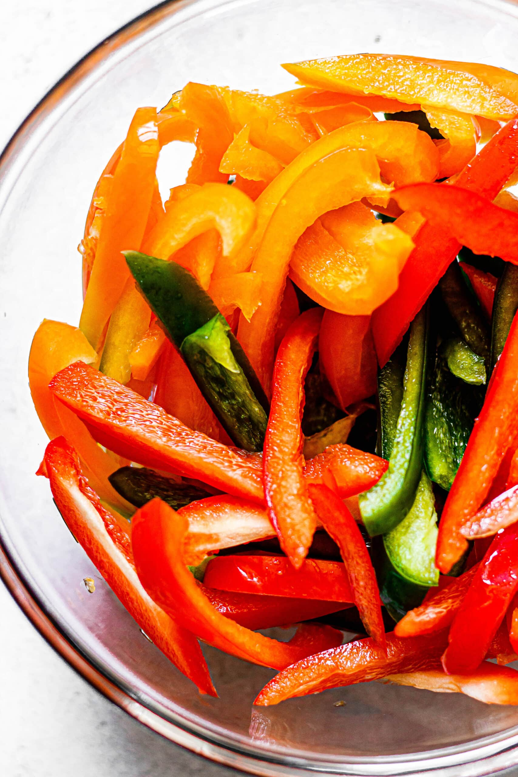 sliced peppers in glass mixing bowl