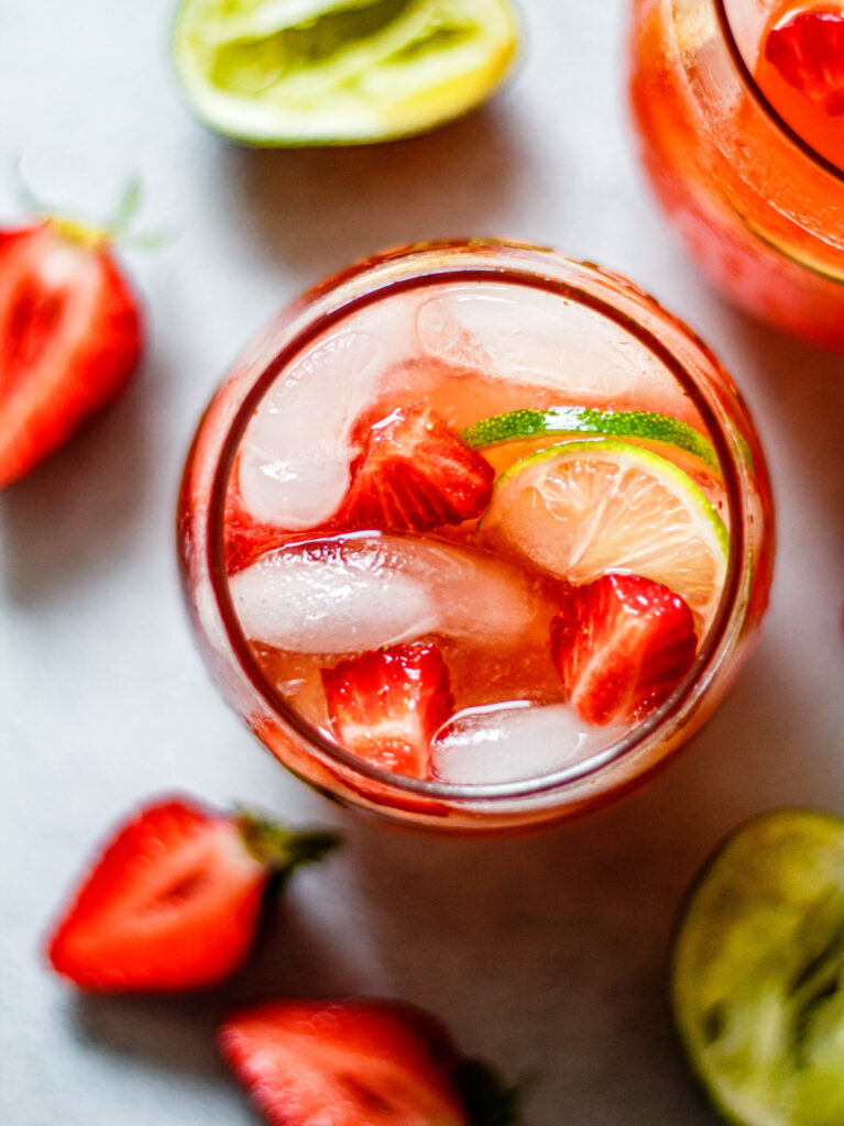 sparkling strawberry limeade in a glass with lemons and limes around the glass
