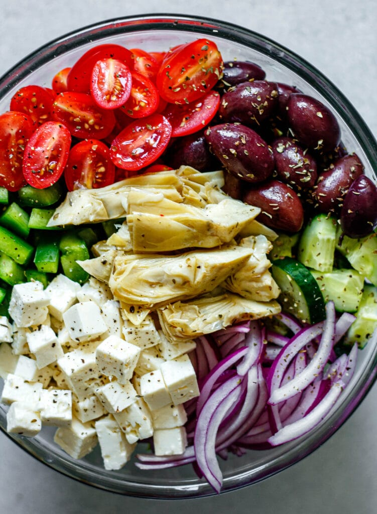 Greek salad ingredients in a large mixing bowl