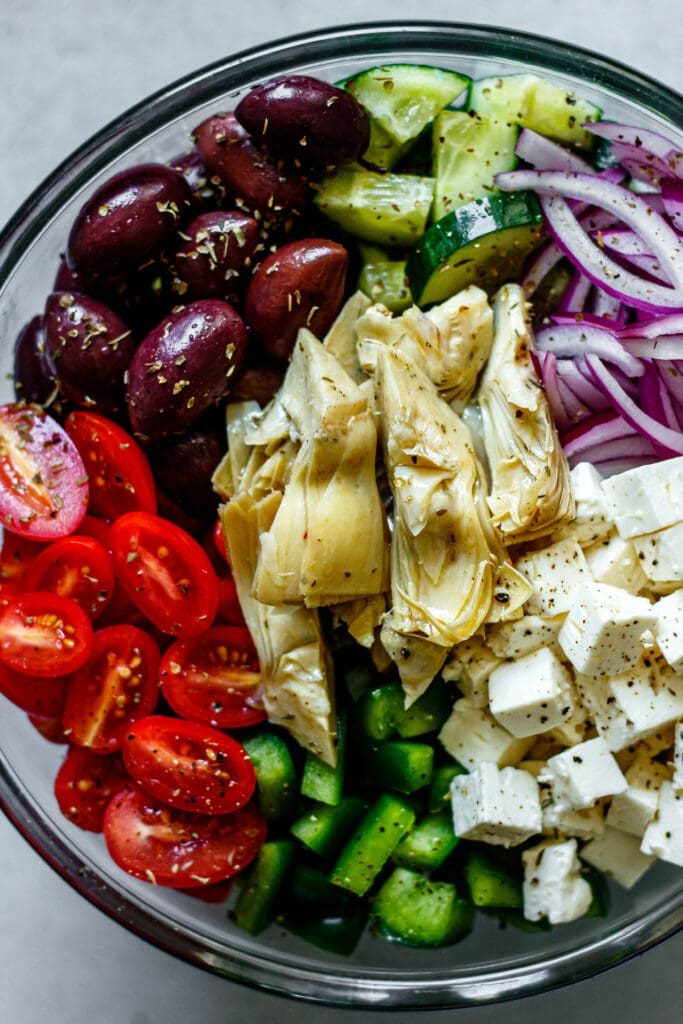 cucumbers, kalamata olives, cucumbers, red onion, tomatoes, green bell pepper, artichokes, feta cheese in a clear mixing bowl