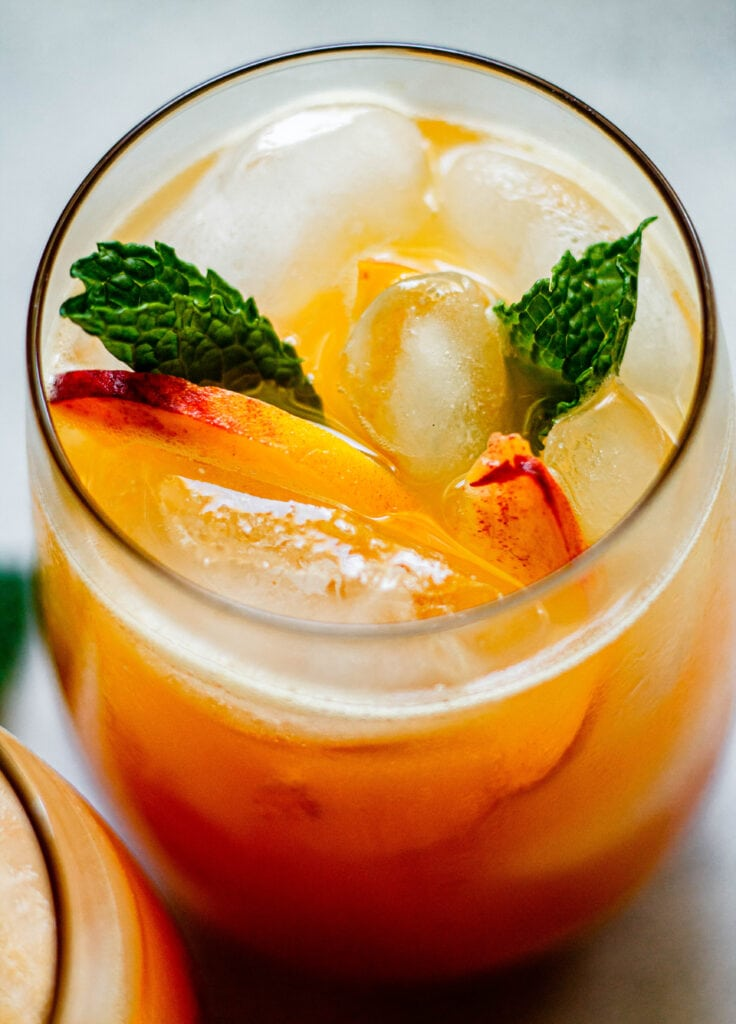 sparkling peach lemonade in a glass with fresh mint and sliced peaches