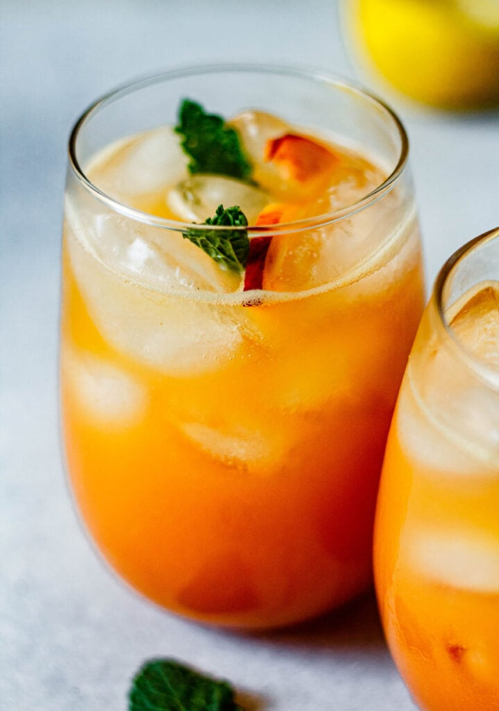 peach lemonade in a glass with fresh mint and sliced peaches with a lemon in the background