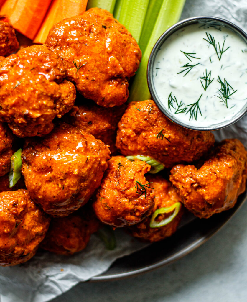 air fryer buffalo cauliflower on a plate with ranch dip, celery, and carrots