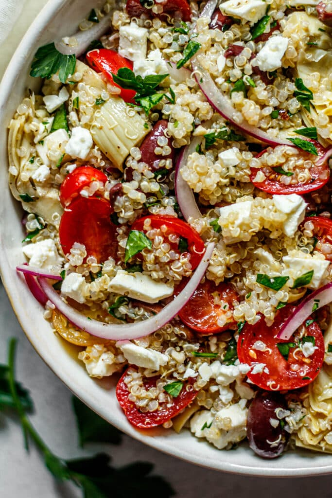 Mediterranean quinoa salad in a white serving bowl