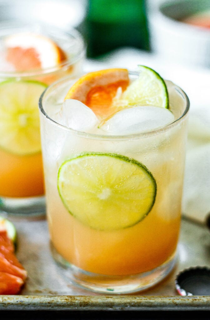 grapefruit paloma in a clear glass with fresh slices of lime and grapefruit
