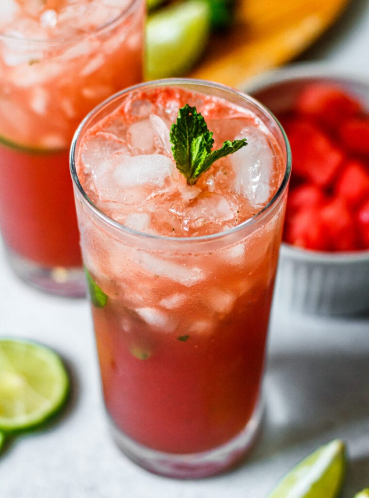 watermelon mojito mocktail in a tall glass with a sprig of fresh mint