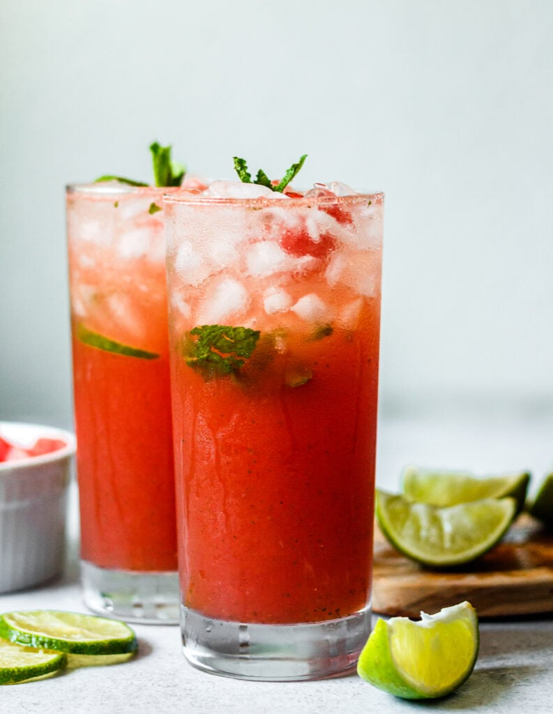 Watermelon Mojito Mocktail in two tall glasses with watermelon and limes in the background