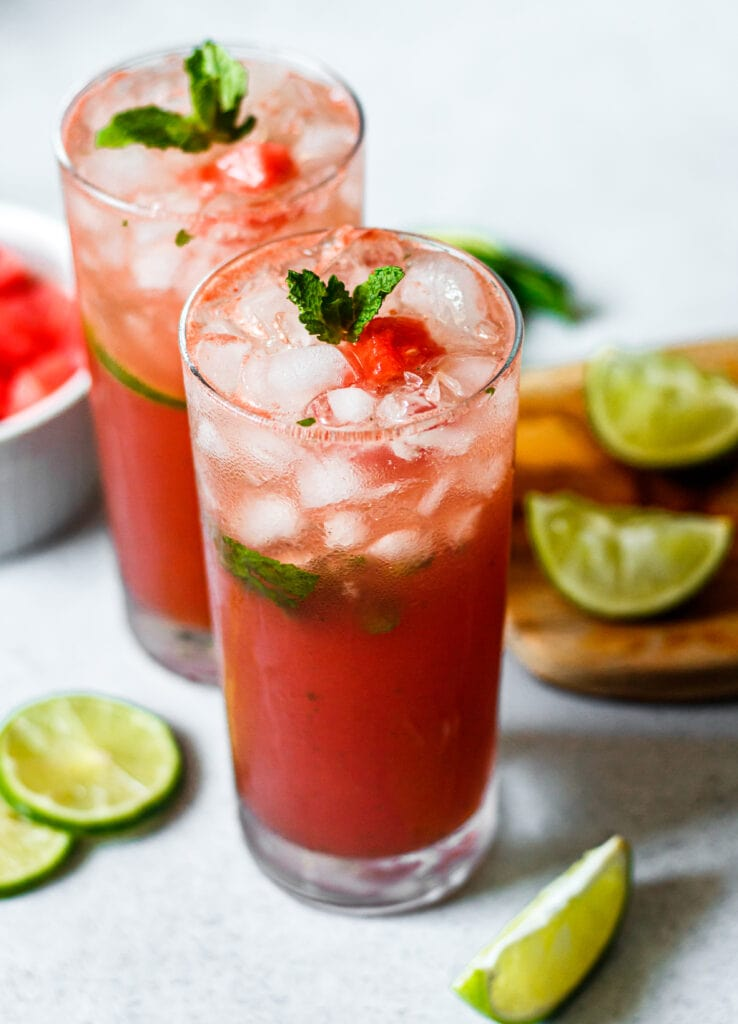 watermelon mojito in two tall glasses with limes and watermelon in the background
