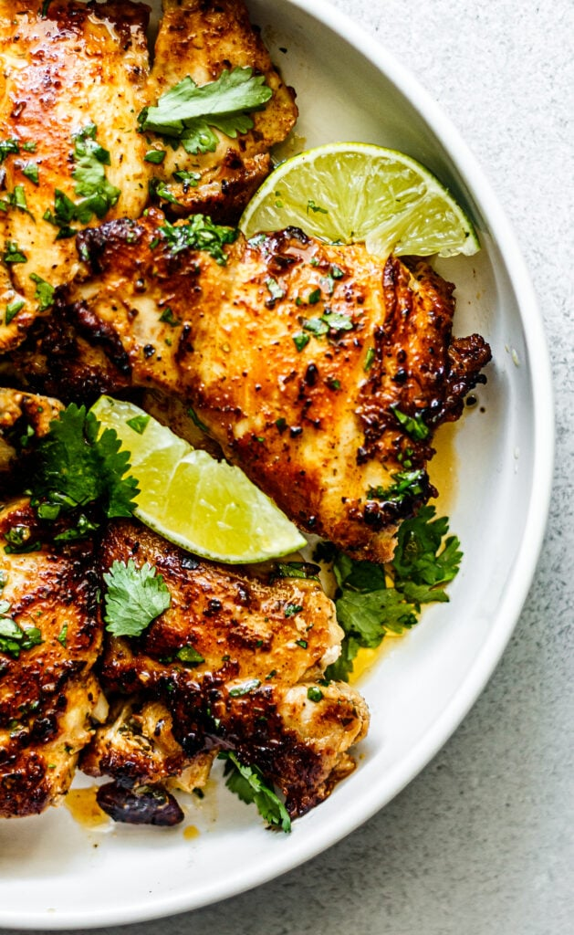 chicken thighs on white plate with lime