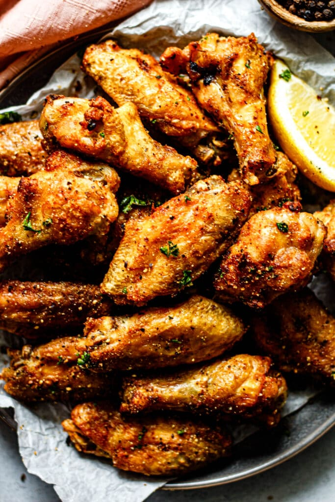baked lemon pepper chicken wings on a plate with parchment paper