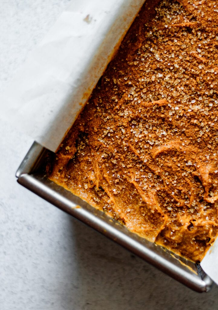 pumpkin bread batter sprinkled with cinnamon sugar in loaf pan with parchment paper