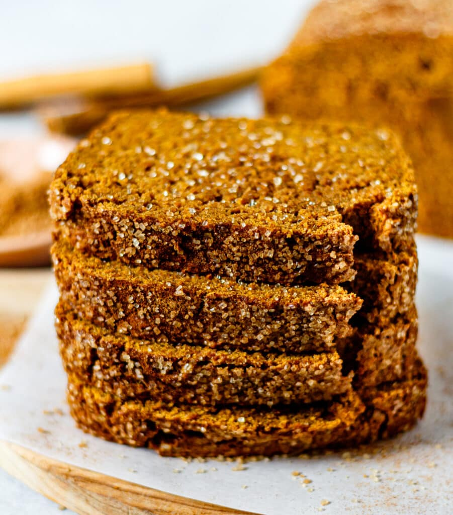 four pumpkin bread slices stacked on each other sprinkled with cinnamon sugar
