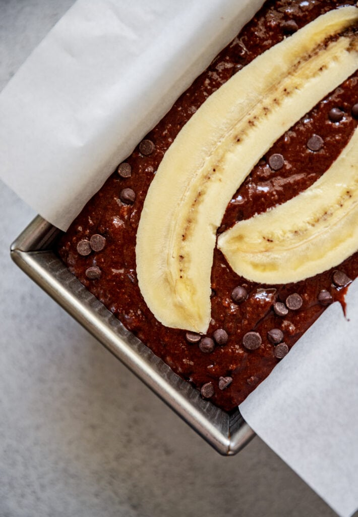 batter in a loaf pan topped with a banana