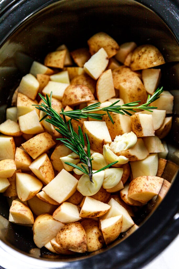 diced potatoes and rosemary in slow cooker