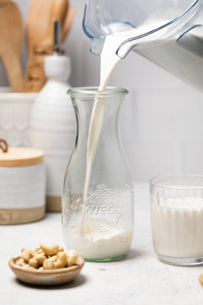 cashew milk being poured in to jar