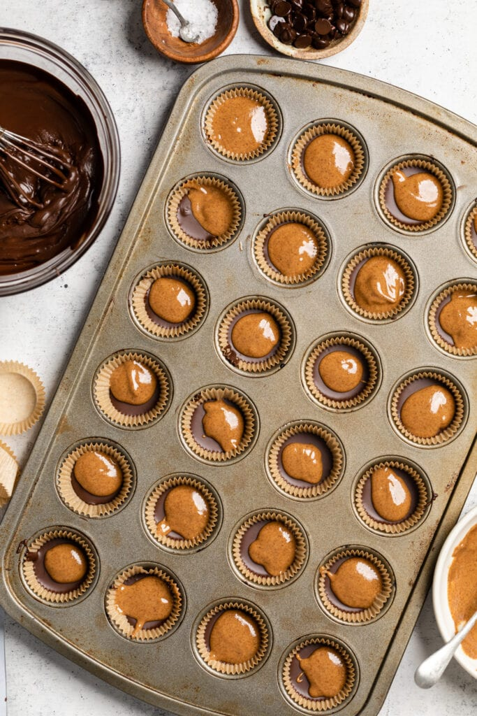 almond butter over chocolate in muffin tray
