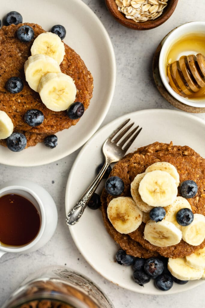 banana oatmeal pancakes on two plates with syrup