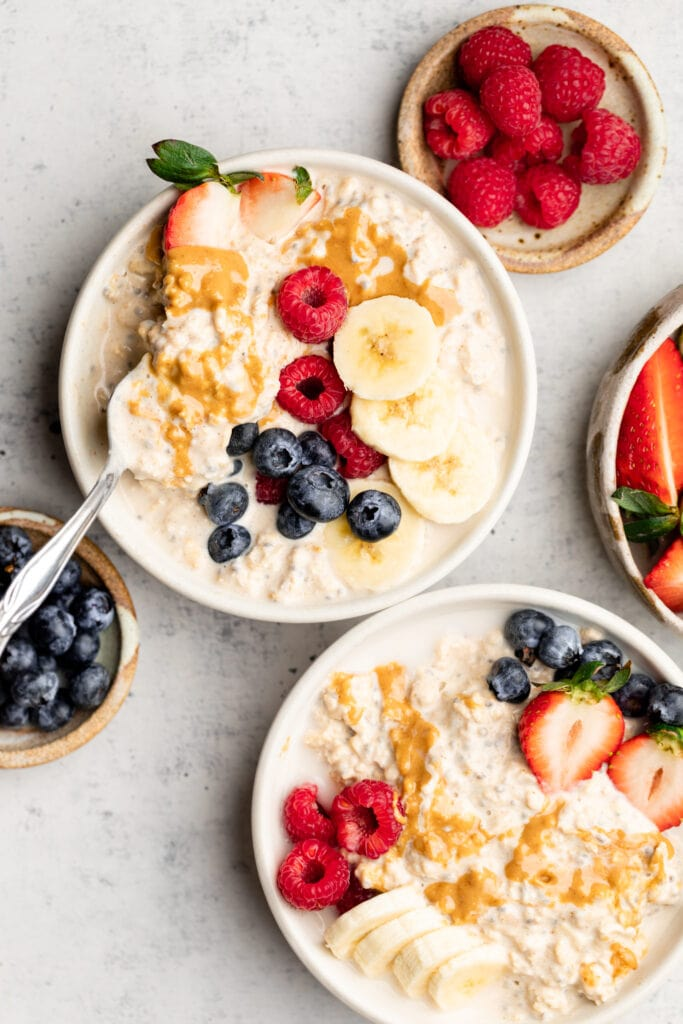 peanut butter overnight oats in bowls topped with fruit