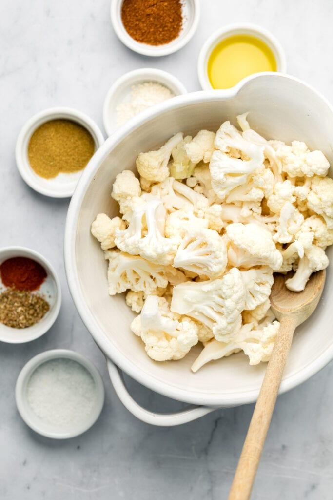 cauliflower in bowl with spices around it