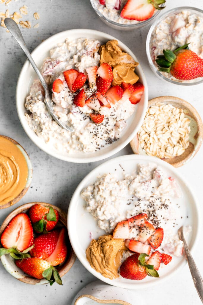 strawberry overnight oats in bowls with toppings