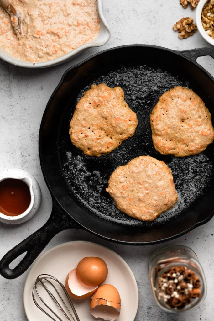 pancakes frying in cast iron skillet