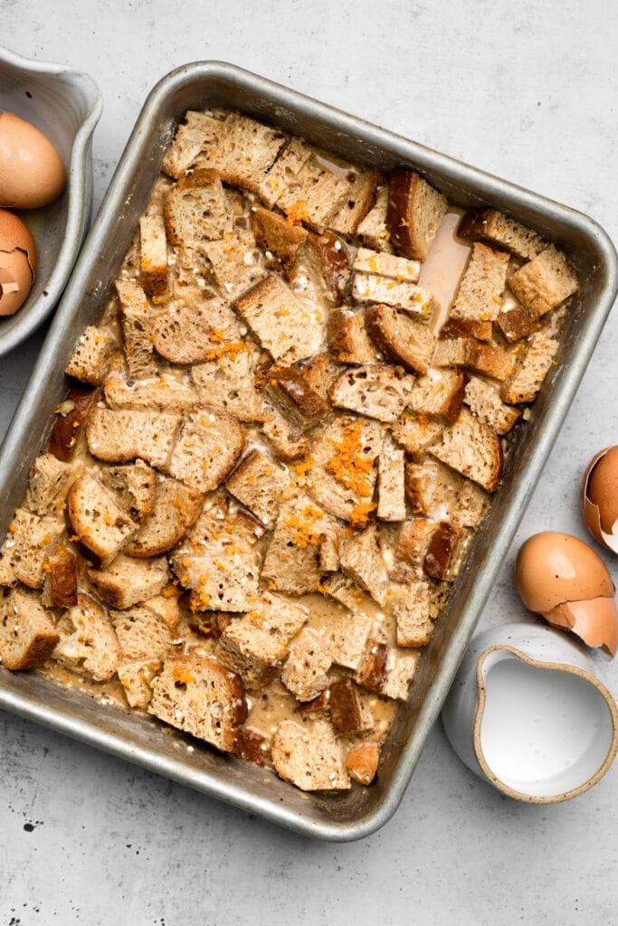 bread soaking in custard in baking dish