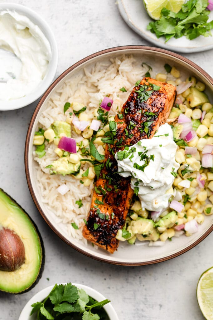 salmon burrito bowl with rice, salsa, and sour cream