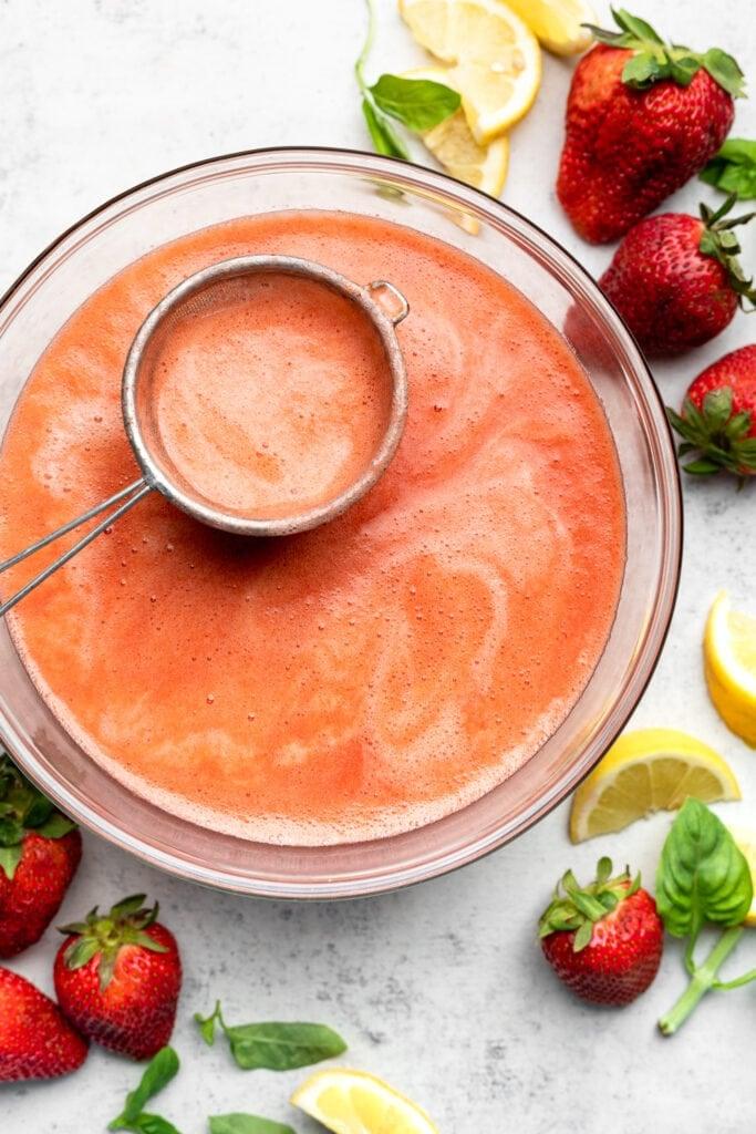 straining the strawberry lemonade in bowl
