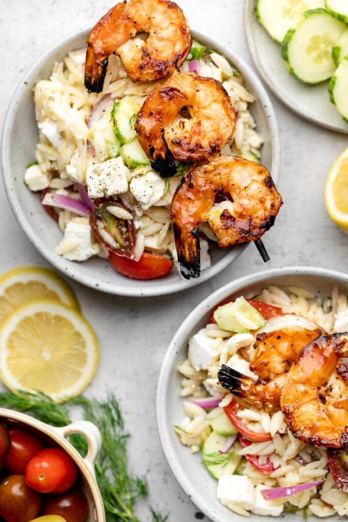 grilled shrimp skewers on top of orzo salad