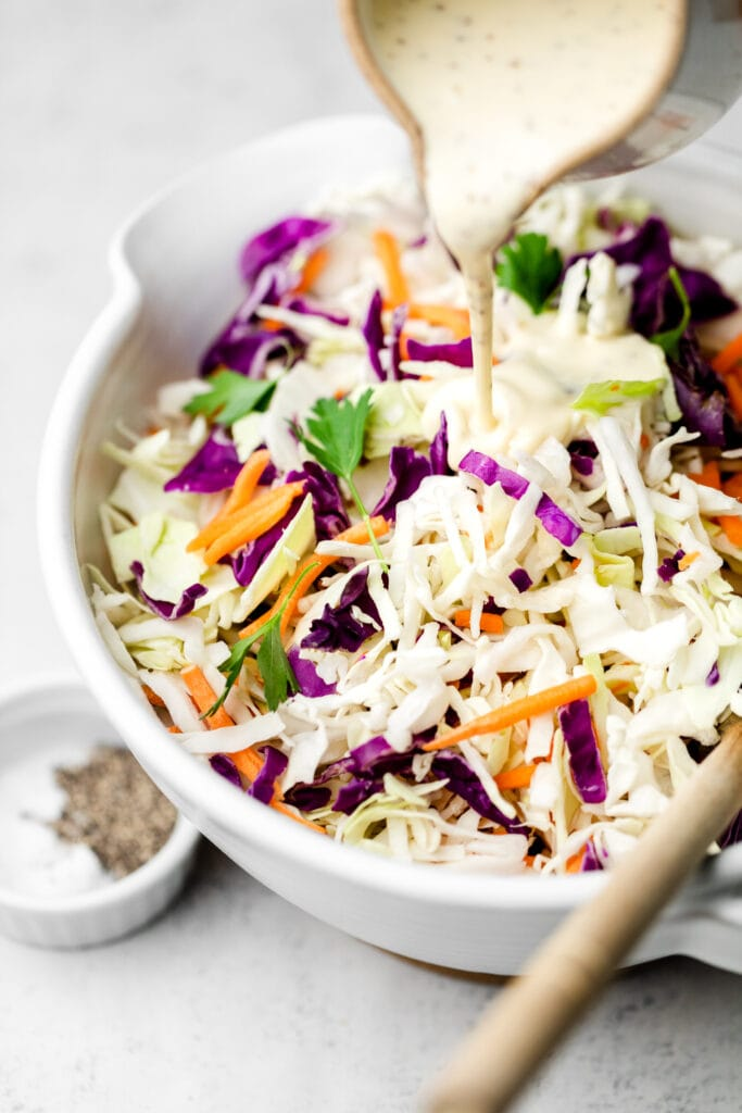 coleslaw dressing being poured onto cabbage