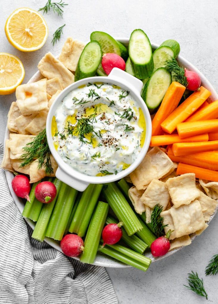 tzatziki sauce in bowl on platter with veggies/pita