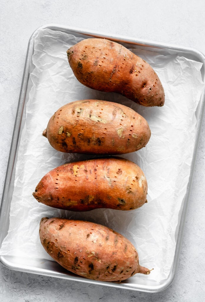 sweet potatoes on sheet pan with parchment paper