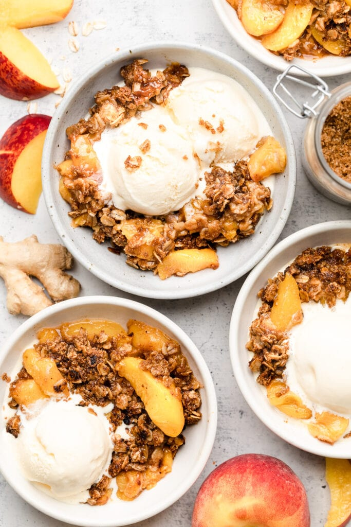 peach crisp served in bowls with ice cream