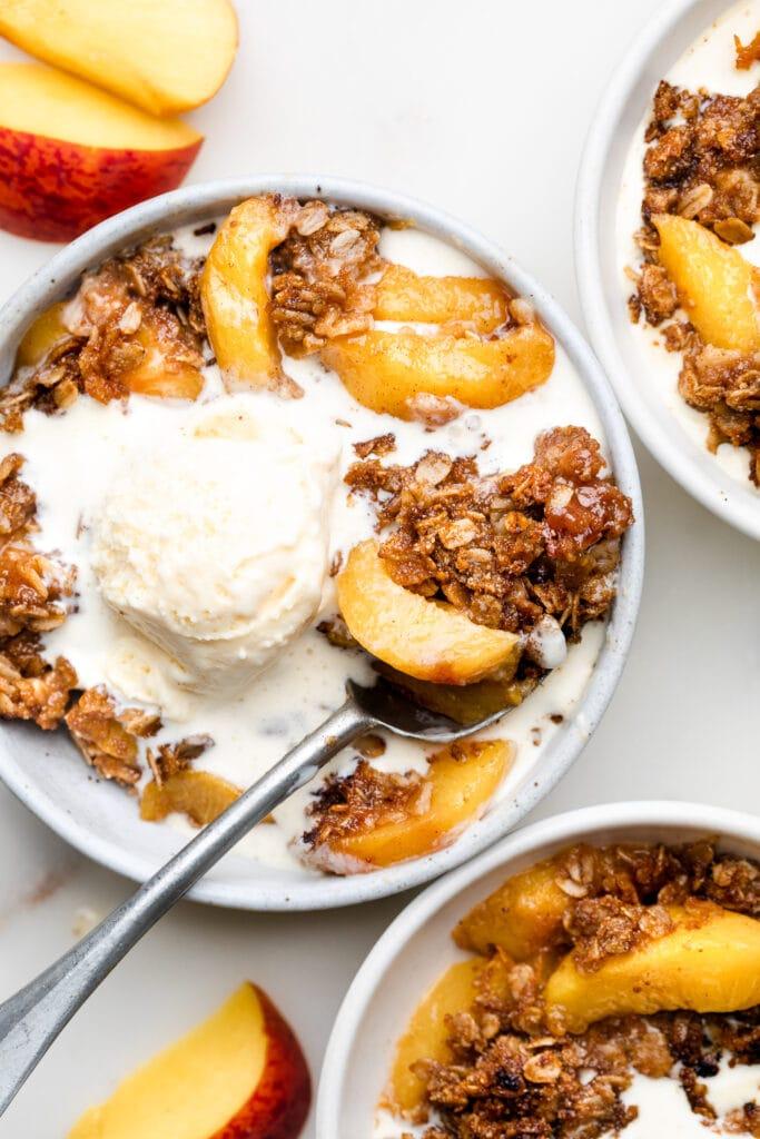 peach crisp in bowl with ice cream