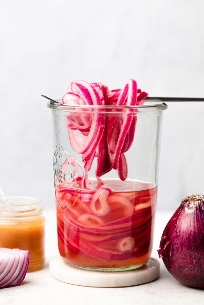 pickled onions on fork in jar