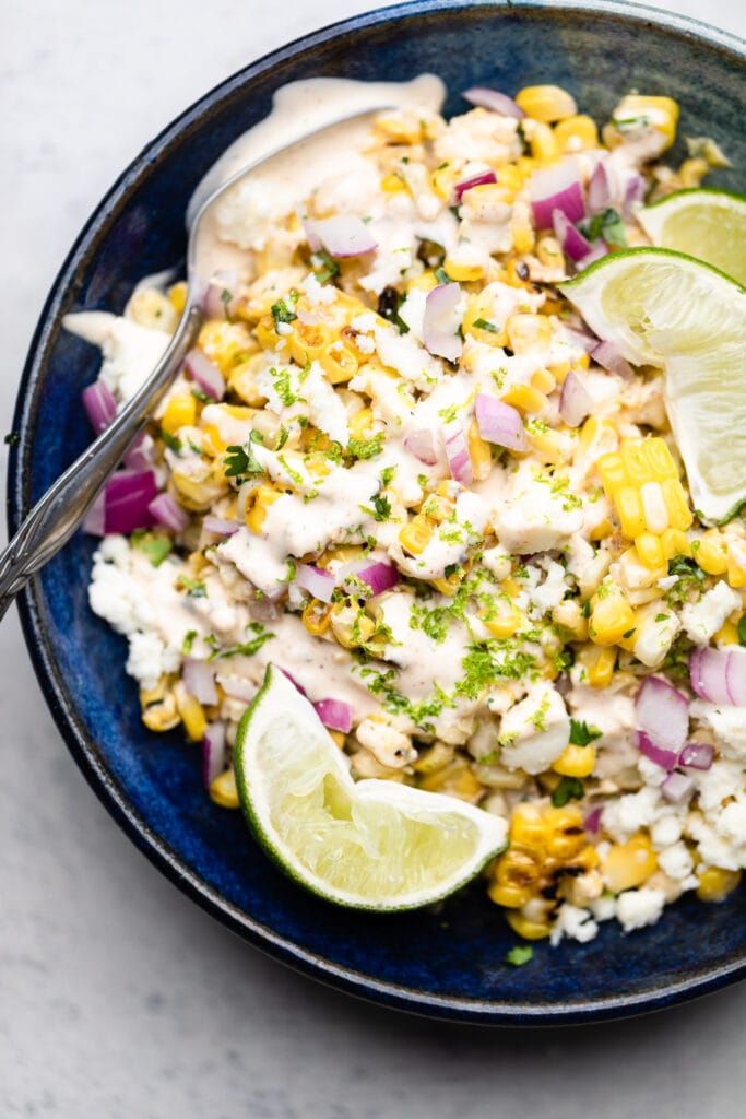 street corn salad in a bowl with lime