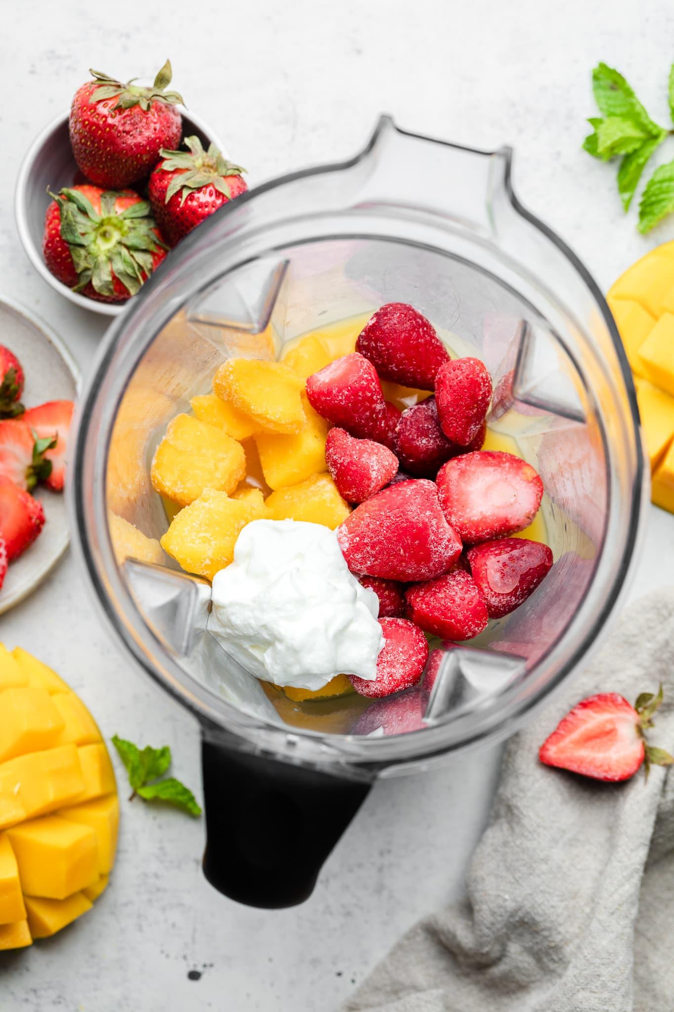 strawberry mango smoothie ingredients in a blender