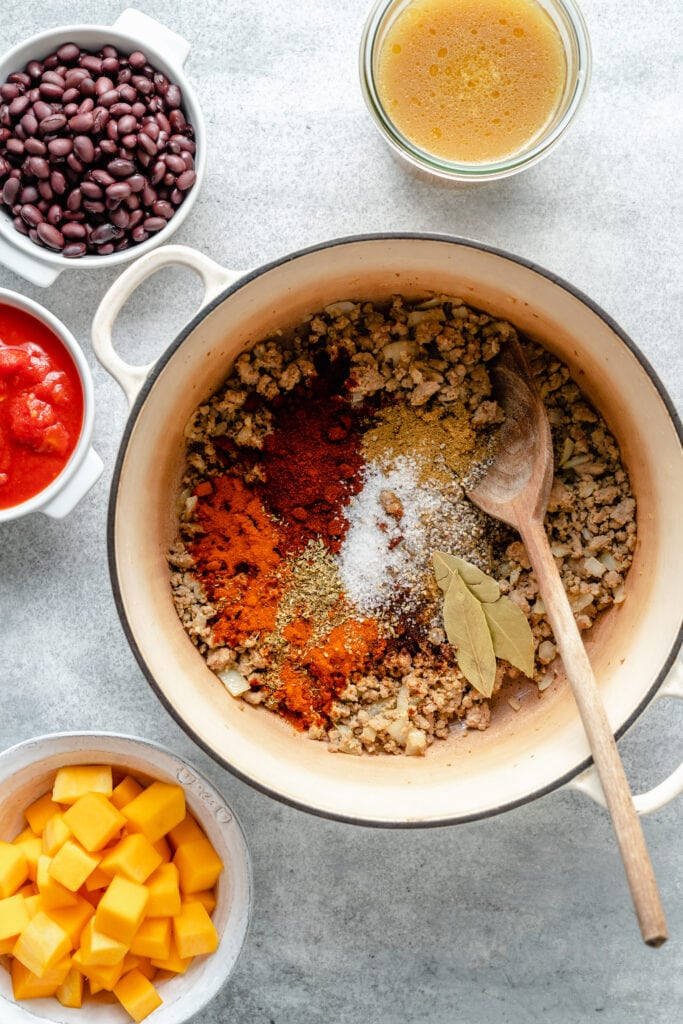 spices, ground beef in pot with wooden spoon