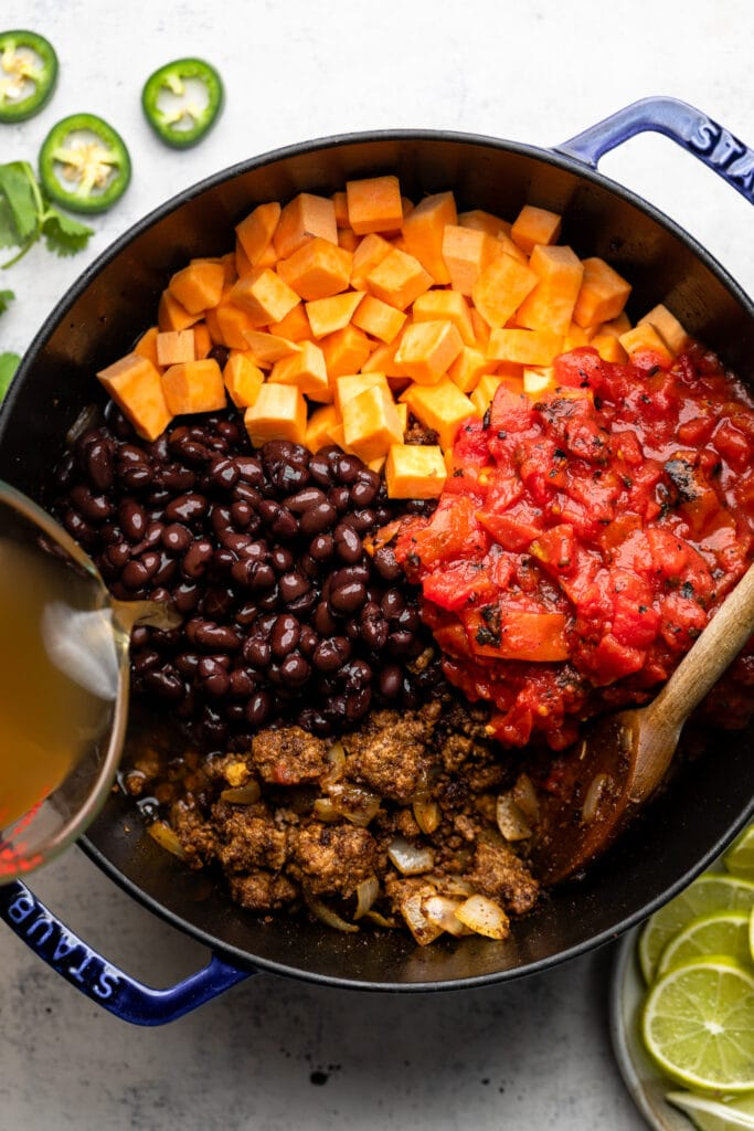 black beans, broth, sweet potato, and tomato in pot