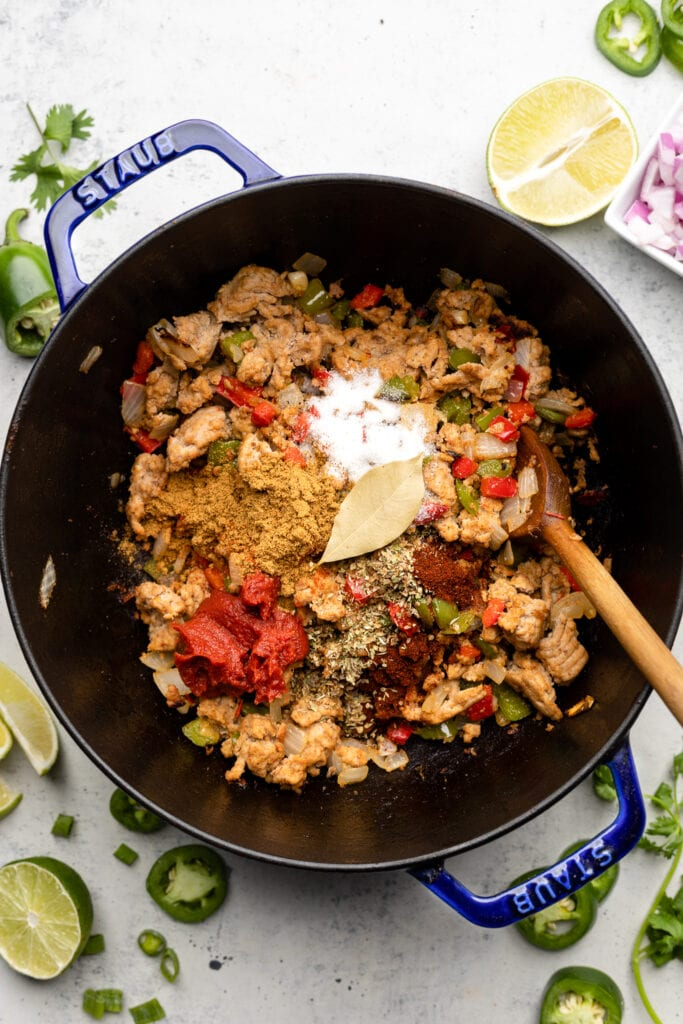 ground turkey, spices, and tomato paste in pot